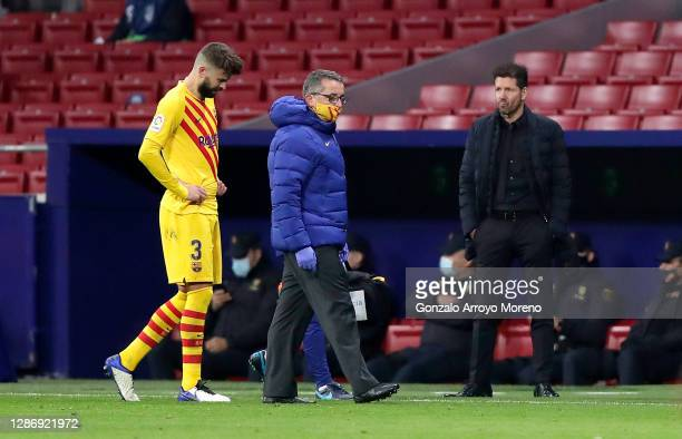 Diego Simeone, Head Coach of Atletico de Madrid looks on as Gerard Pique of FC Barcelona looks dejected following his team's defeat in the La Liga...