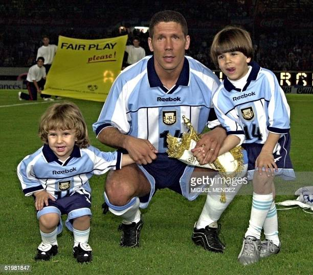 Diego Simeone pauses with his children Giovanni and Gianluca after he received a silver plate for playing 100 matches for Argentina in the Monumental...