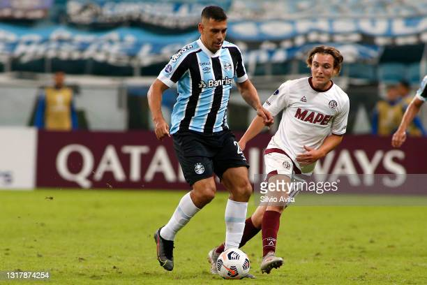 Diego Souza of Gremio competes for the ball with Pedro De la Vega of Lanus during a match between Gremio and Lanus as part of group H of Copa...
