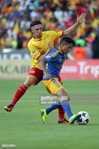 Diego Valdes of Morelia vies for the ball with Javier Aquino of Tigres during their Mexican Apertura 2016 tournament football match at the Jose Maria...