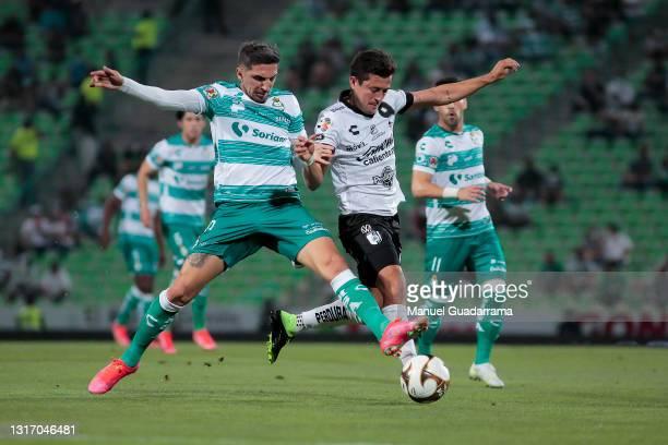 Diego Valdes of Santos struggles for the ball with Fernando Madrigal of Queretaro during the playoff match between Santos Laguna and Queretaro as...