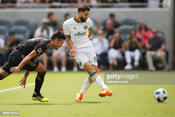 Diego Valeri of the Portland Timbers takes a shot on goal trailed by Benny Feilhaber of the Los Angeles Football Club at Banc of California Stadium...