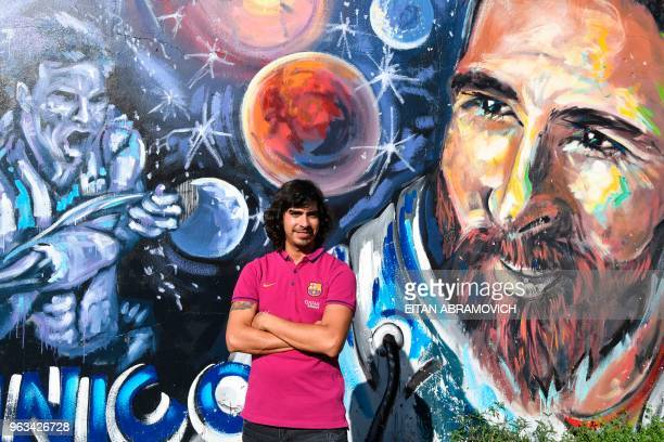 Diego Vallejos childhood friend of Argentine football star Leonel Messi poses for a picture in front of a mural depicting the footballer during an...