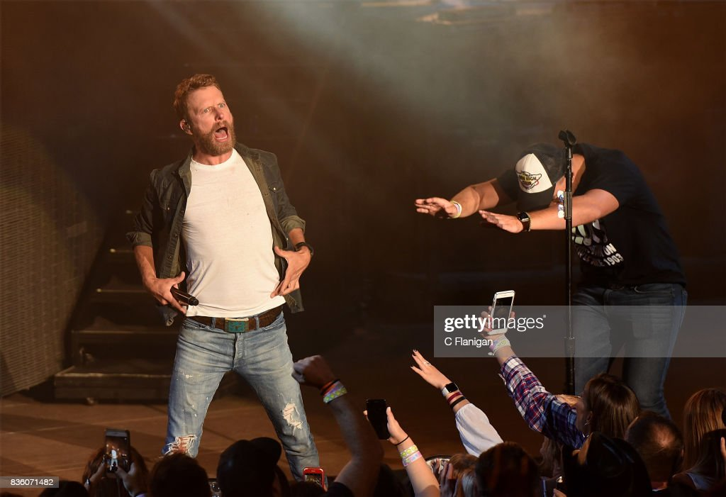 Dierks Bentley brings a fan onstage to 'shotgun' a beer during his 'What The Hell' world tour at Shoreline Amphitheatre on August 20, 2017 in Mountain View, California.
