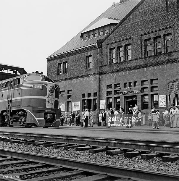 A diesel locomotive and passengers on the platform at New London United States 1954