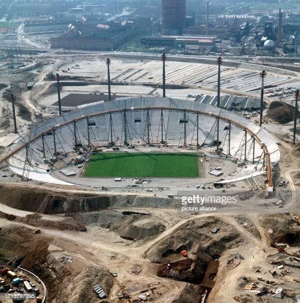 Dieses von erhöhtem Standpunkt aus im Frühjahr 1971 aufgenommene Foto zeigt das Olympiastadion von München bereits in deutlich wahrnehmbaren...