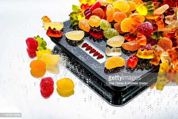 diet jelly sweet on a black balance with hearts display (weingummi ) - spiegelung stock pictures, royalty-free photos & images