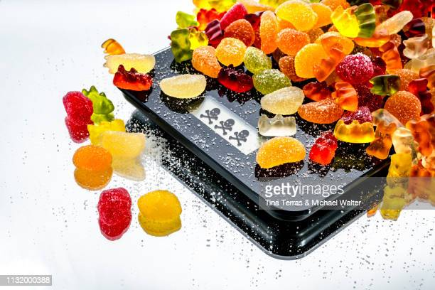 diet jelly sweet on a black balance with skull display (weingummi) - food contamination stock photos and pictures