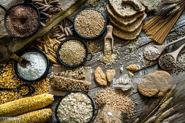 dietary fiber: large group of wholegrain food shot on rustic wooden table - buckwheat stock pictures, royalty-free photos & images