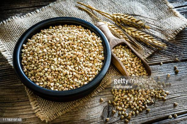 dietary fiber: wholegrain buckwheat in a black bowl on rustic wooden table - buckwheat stock pictures, royalty-free photos & images