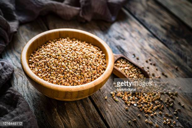 dietary fiber: wholegrain buckwheat in a wooden bowl on rustic kitchen table - buckwheat stock pictures, royalty-free photos & images
