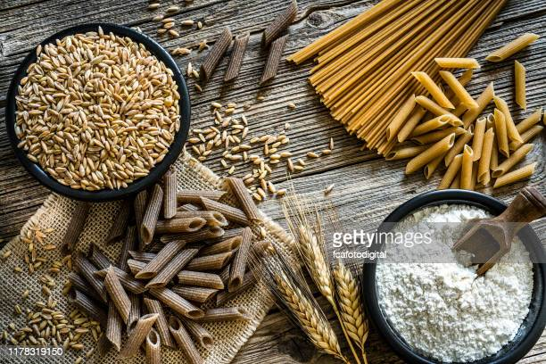 dietary fiber: wholegrain pasta, spelt and flour on rustic wooden table - wholegrain stock pictures, royalty-free photos & images