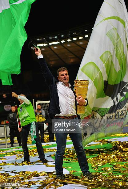 Dieter Hecking head coach of Wolfsburg holds the trophy as he waves to the fans after winning the DFB Cup Final between Borussia Dortmund and VfL...