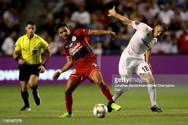Dieter Villalpando of Chivas de Guadalajara dribbles the ball while being defended by Sebastian Cristoforo of ACF Fiorentina in the first half during...