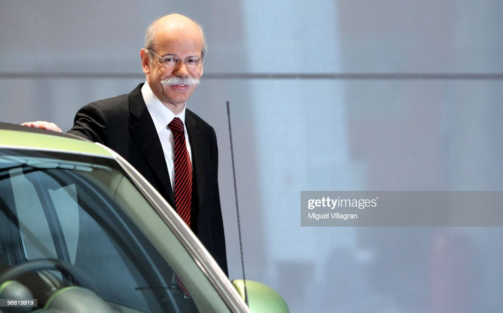 Dieter Zetsche, CEO of Daimler AG, poses next to a smart electric car during the company's annual press conference on February 18, 2010 in Stuttgart, Germany. Daimler reported it lost money in the fourth quarter of 2009 and was canceling dividends for the first time in more than a decade.