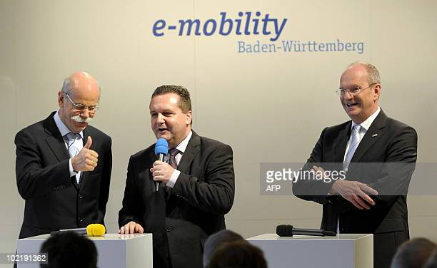 Dieter Zetsche CEO of the Daimler AG thumbsup as he stands on a podium with Stefan Mappus governor of the southern federal state of BadenWuerttemberg...
