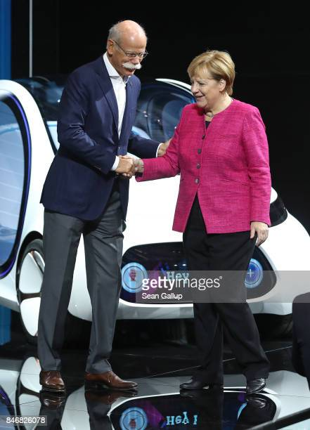 Dieter Zetsche Chairman of Daimler AG greets German Chancellor Angela Merkel in front of a Smart Vision EQ Fortwo autonomous electric concept car...