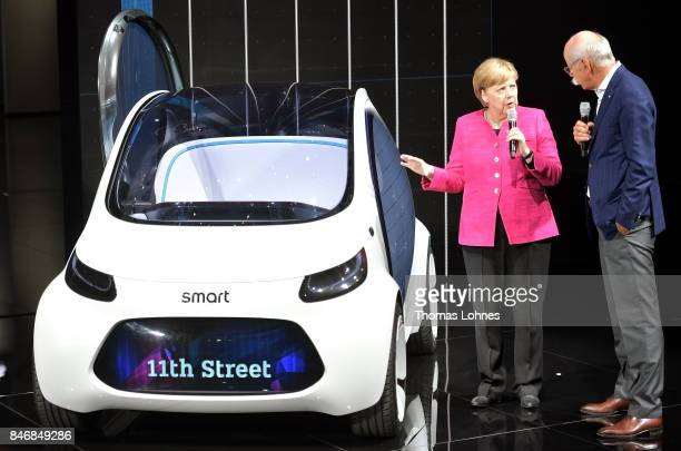 Dieter Zetsche Chairman of Daimler AG shows the German Chancellor Angela Merkel a Smart Vision EQ concept car during her visit at the 2017 Frankfurt...