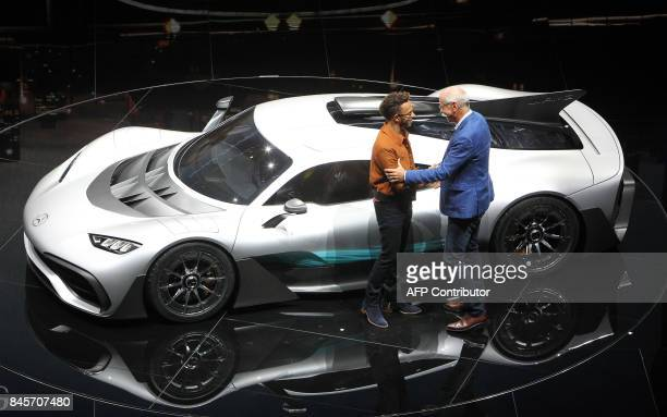 Dieter Zetsche chairman of German car maker Daimler AG and head of MercedesBenz cars and Mercedes' British driver Lewis Hamilton pose in front of a...