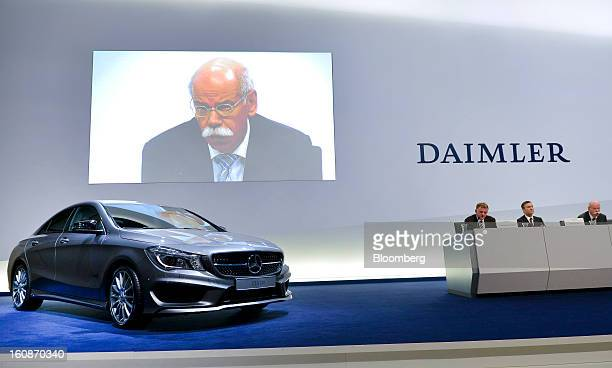 Dieter Zetsche chief executive officer of Daimler AG is seen on a large video screen above a MercedesBenz CLA 180 automobile as he speaks during a...
