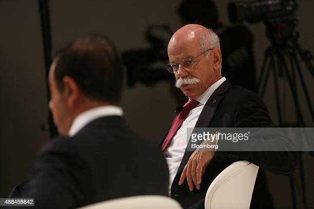 Dieter Zetsche chief executive officer of Daimler AG right listens as Carlos Ghosn chief executive officer of Renault SA and Nissan Motor Co speaks...