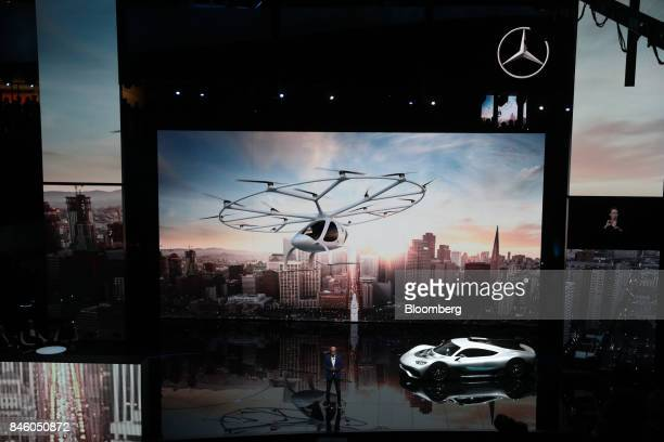 Dieter Zetsche chief executive officer of Daimler AG speaks beside a MercedesBenz AMG Project One hypercar and a video screen showing a Mercedes...