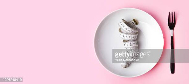 dieting and health care concept. plate and cutlery with measuring tape. measure tape on white plate, pink background. flat lay and copy space for text. the concept of harmony and weight loss after self-isolation. - fasting activity stock pictures, royalty-free photos & images