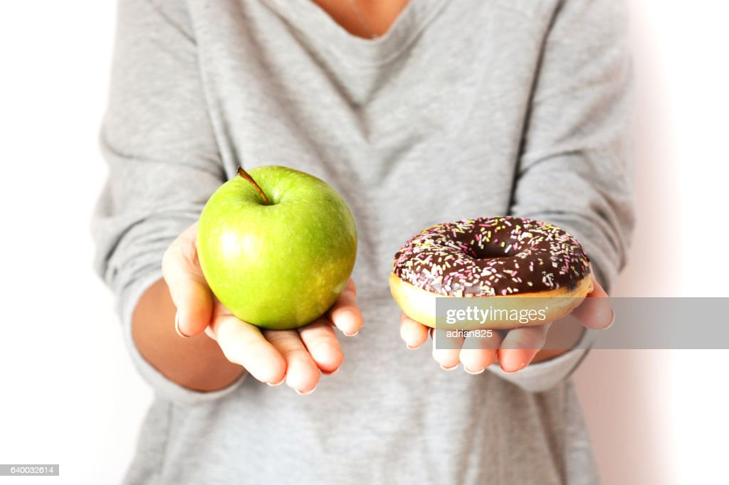 Dieting concept with woman choosing between healthy fruits and donut : Stock Photo