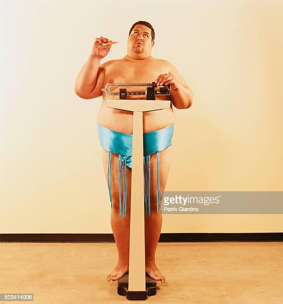 Dieting Sumo Wrestler Weighing Himself