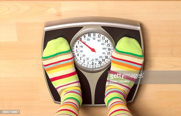 dieting woman on bathroom scales - oversized stock pictures, royalty-free photos & images