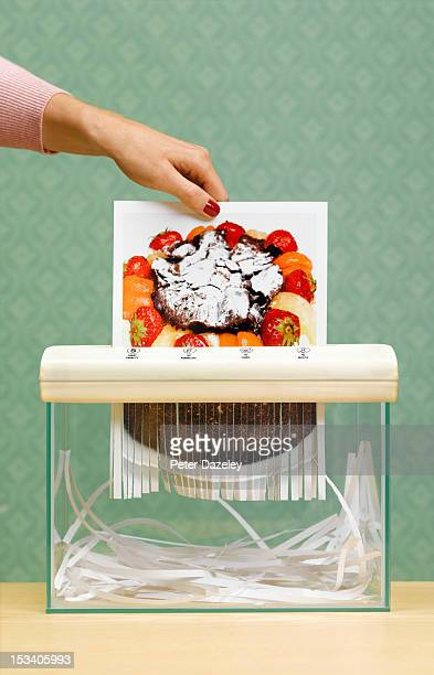 Dieting woman shredding image of cake