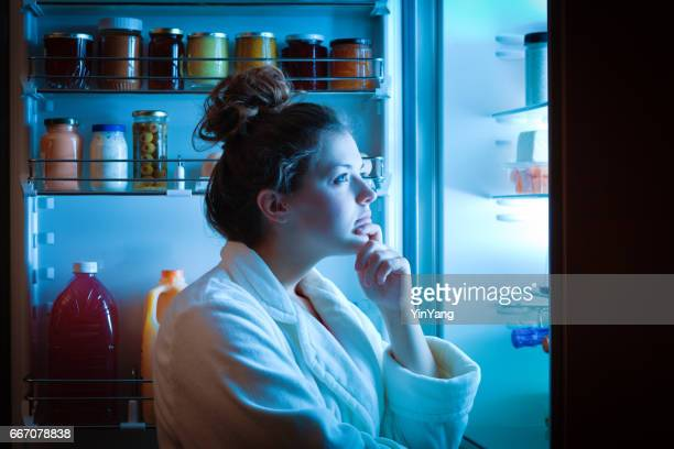 dieting young woman late night making choices on what to eat - unhealthy living stock pictures, royalty-free photos & images