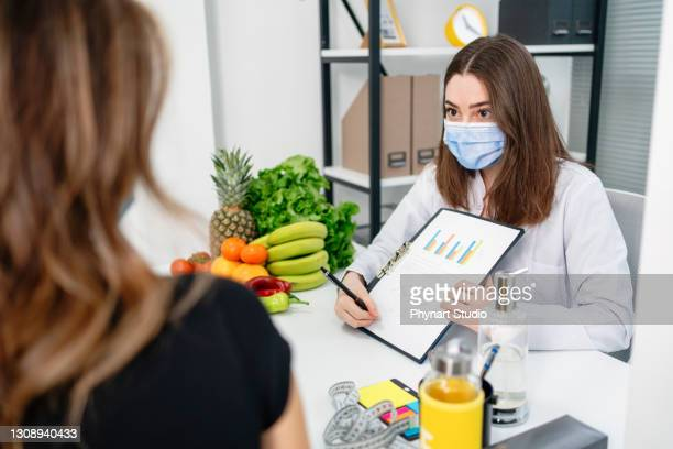 dietitian holding diet plan during consultation with patient in the office - fat nutrient stock pictures, royalty-free photos & images