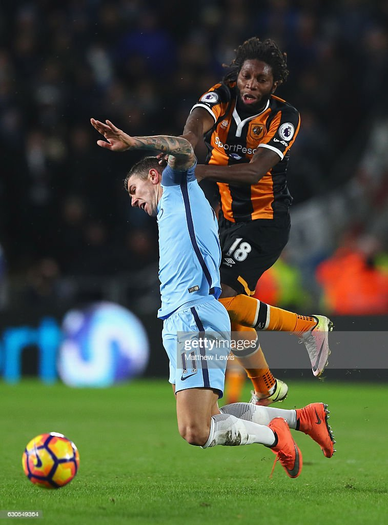 Dieumerci Mbokani of Hull City challenges Aleksandar Kolorov of Manchester City during the Premier League match between Hull City and Manchester City at KCOM Stadium on December 26, 2016 in Hull, England.