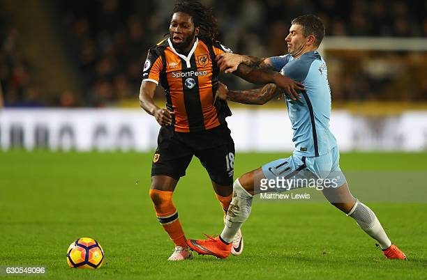 Dieumerci Mbokani of Hull City is challenged by Aleksandar Kolorov of Manchester City during the Premier League match between Hull City and...