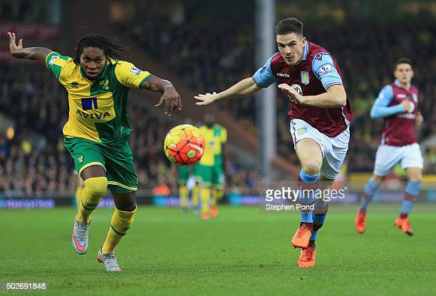 Dieumerci Mbokani of Norwich City and Ciaran Clark of Aston Villa compete for the ball during the Barclays Premier League match between Norwich City...