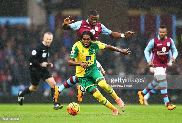 Dieumerci Mbokani of Norwich City and Jores Okore of Aston Villa compete for the ball during the Barclays Premier League match between Aston Villa...