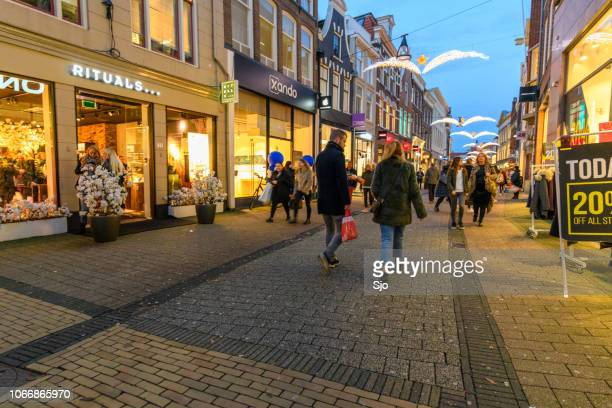 diezestraat shopping street in zwolle during a cold winter night, people are walking on the street and looking at the shop windows. - high street stock pictures, royalty-free photos & images