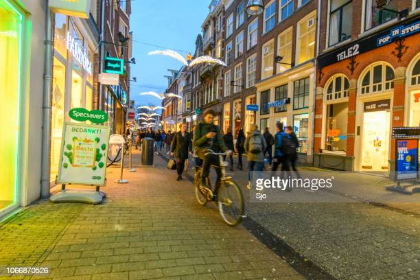 diezestraat shopping street in zwolle during a cold winter night, people are walking on the street and looking at the shop windows. - zwolle stock pictures, royalty-free photos & images