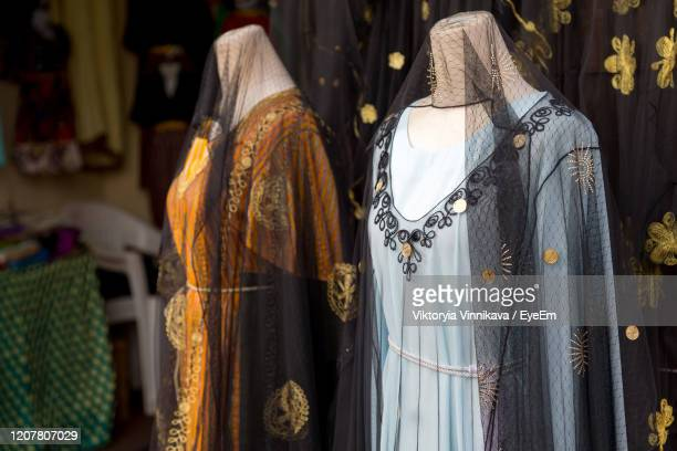 different abaya style dresses displayed in the shop in dubai souq - expense stock pictures, royalty-free photos & images