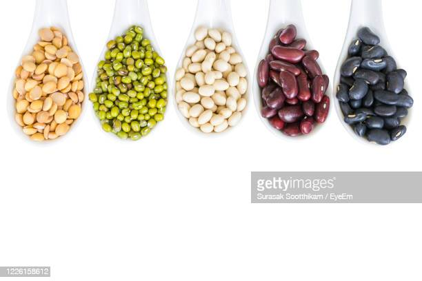 different beans in white spoon isolated on white - legume family stock pictures, royalty-free photos & images