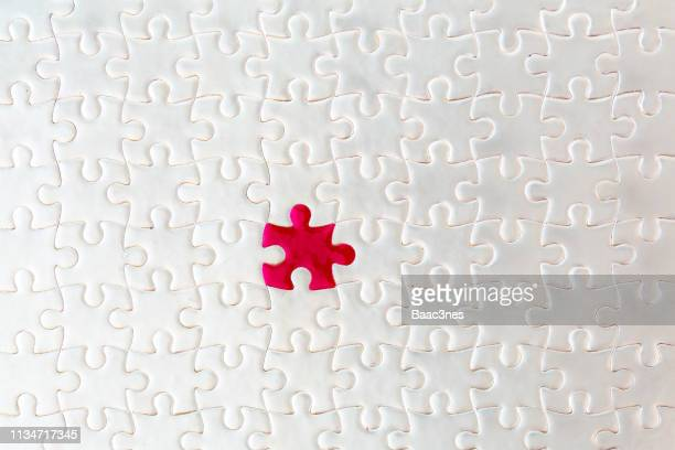 different, but still a good match. red puzzle fits together with white puzzle pieces - finishing stock pictures, royalty-free photos & images