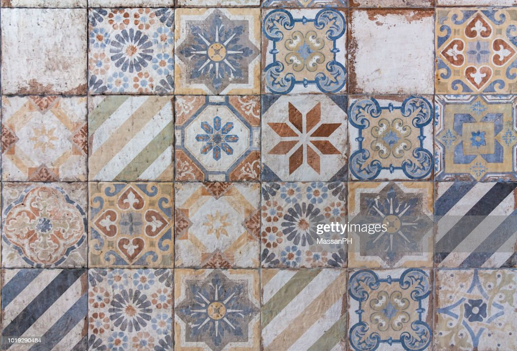 Different ceramic tiles with mediterranean style patterns in orange and blue on a wall : Stock Photo