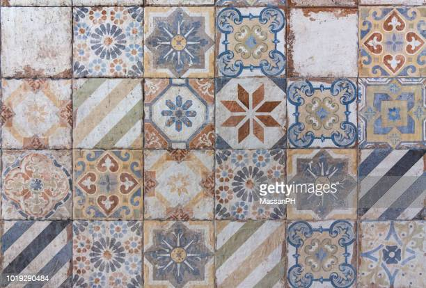 Different ceramic tiles with mediterranean style patterns in orange and blue on a wall