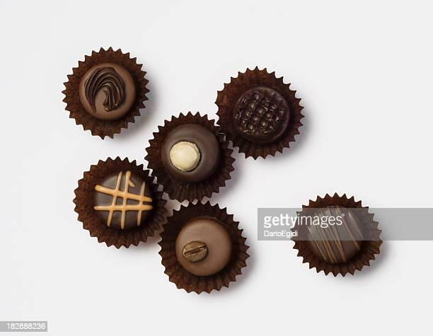 Different chocolate pralines on white background