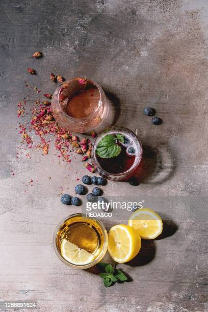 Different cocktail glasses with sparkling colorful drinks pink rose champagne, cider or lemonade with dry rose buds, lemon, blueberries and mint....