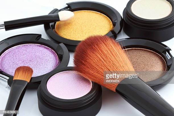 Different color cosmetic powders on white background
