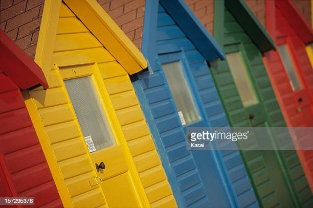 Different colored beach huts all in a line