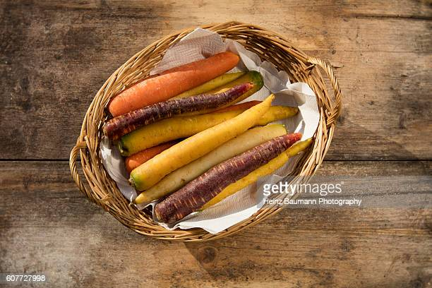 Different colored carrots in a basket on a weathered garden table
