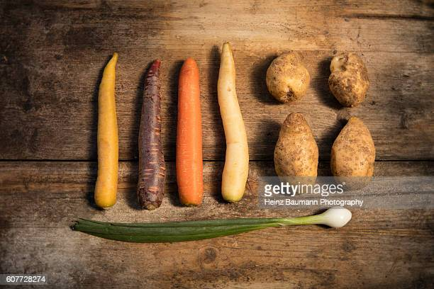 Different colored carrots with onion and agria potatoes on a weathered garden table